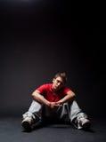 Breakdancer sitting on the floor. Breakdancer in red t-shirt sitting on the floor stock photography