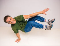 Breakdancer. Skilful breakdancer doing moves while performing a handstand over white background Royalty Free Stock Images