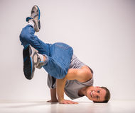Breakdancer. Skilful breakdancer posing on his hands at studio over white background Royalty Free Stock Image