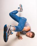 Breakdancer. Skilful breakdancer posing on his hands at studio over white background royalty free stock images