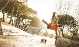 Breakdancer urbano del atleta que realiza tirón acrobático del salto en el skatepark Foto de archivo