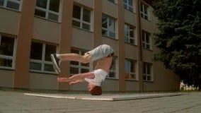 Breakdancerrotaties op zijn hoofd op de slowmotion straat, stock video