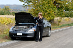 Breakdown. Businesswoman And Her Car Stranded By The Side Of The Road, Calling For Help On A Cellphone Royalty Free Stock Photos