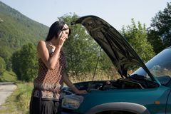Breakdown of car. Woman breaking down of car and discussing with her telephone Royalty Free Stock Photos