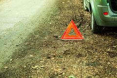 Breakdown of car. Red warning triangle sign on road. Car transportation. Breakdown of car transporation. Closeup of red warning triangle sign symbol on the Stock Photography