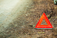Breakdown of car. Red warning triangle sign on road. Car transportation. Breakdown of car transporation. Closeup of red warning triangle sign symbol on the Stock Image
