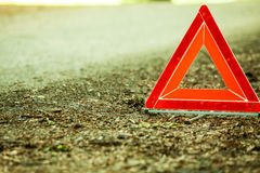 Breakdown of car. Red warning triangle sign on road. Car transportation. Breakdown of car transporation. Closeup of red warning triangle sign symbol on the Stock Photo