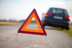 Breakdown triangle stands on a broken car Royalty Free Stock Photos
