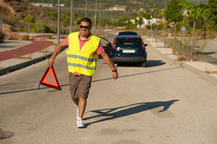 Breakdown trouble. Guy carrying a triangle to warn of his breakdown Royalty Free Stock Photo