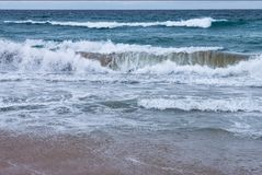 Breakers rushing onto the shore with spray and foam on a stormy day at the beach stock image