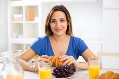 吃breakfa的年轻美丽的愉快的微笑的妇女新月形面包 免版税库存图片