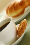 Breakfast 07. Fresh-baked croissant, cookies and cup of coffee. Shallow DOF. Focus on cup and cookies Stock Photos
