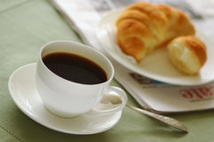 Breakfast 09. Fresh-baked croissant, cup of coffee and newspaper. Shallow DOF. Focus on cup Stock Photos
