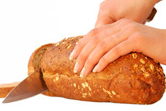 Before breakfast. Hand cutting bread  isolated on white Stock Images