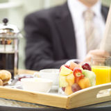 At breakfast. Business man sitting in his hotel room enjoying breakfast and the paper Royalty Free Stock Images