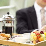 At breakfast. Business man sitting in his hotel room enjoying breakfast and the paper Royalty Free Stock Photos
