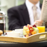 At breakfast. Business man sitting in his hotel room enjoying breakfast and the paper Royalty Free Stock Photography