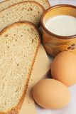 Breakfast. Eggs and a cup of milk. Slices of bread on wooden plate Stock Photography
