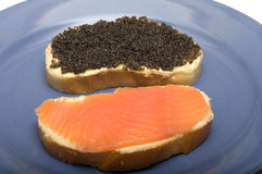 Breakfast. Sandwiches with red fish and black caviar on a blue plate Royalty Free Stock Photo