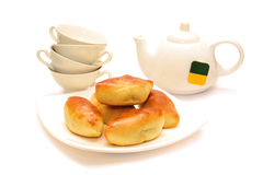 Breakfast. Patty on a plate against the background of the teapot and cups Stock Photo
