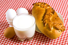 Breakfast. Of eggs, a cup of milk and a pie on a red tablecloth Royalty Free Stock Image