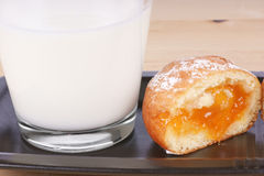 Breakfast. A cup of milk and a half freshly made Berliner with apricot jam and powdered sugar. Studio shot Stock Image