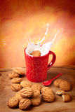 Breakfast. Delicious cookie falling into a cup of milk with big splash Stock Photography