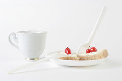Breakfast. Morning dessert. Slices of bread and butter with Far-East cherries on white plate with spoon and fork. Cup of tea Royalty Free Stock Photo