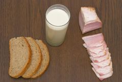 Breakfast. Milk in a glass, the cut bread and bacon Royalty Free Stock Photos
