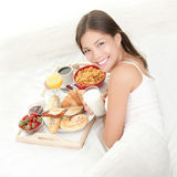 Breakfast. In bed. Young woman eating  in bed drinking milk. Beautiful young woman smiling Royalty Free Stock Photos