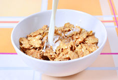 Breakfast. Milk pouring into cereal on check tablecloth royalty free stock images