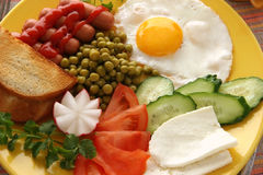Breakfast. Dish with fried egg, frankfurters, vegetables and cheese Royalty Free Stock Photography