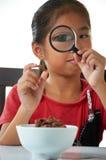 Breakfast. Asian girl looking through magnifier on her breakfast Stock Photos