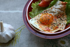 Breakfast. Fried egg with salad, tomato  and garlic in country style Stock Photo