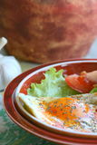 Breakfast. Fried egg with salad, tomato  and garlic in country style Royalty Free Stock Photography