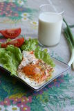 Breakfast. Fried egg with salad, tomato and glass of milk in country style Stock Photography