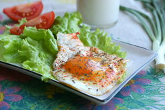 Breakfast. Fried egg with salad, tomato and glass of milk in country style Royalty Free Stock Photos
