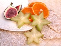 Breakfast. On diet - figs, carambola, oranges and rice-cakes Stock Photography