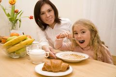 Breakfast. Young woman and her daughter have a breakfast Royalty Free Stock Image