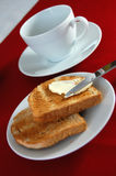 Breakfast. Two slices of toast, a knife spreading the butter and a tea cup Royalty Free Stock Image