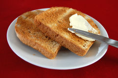 Breakfast. Two slices of toast on a white plate and a knife spreading the butter Stock Photo