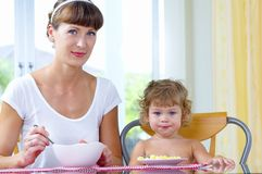 Breakfast. Portrait of young woman feeding her baby daughter Stock Image