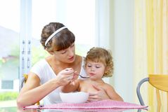 Breakfast. Portrait of young woman feeding her baby daughter Royalty Free Stock Photo