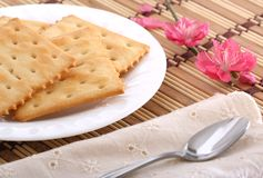 Breakfast. Crackers on a white plate and a spoon on dinner cloth Royalty Free Stock Image