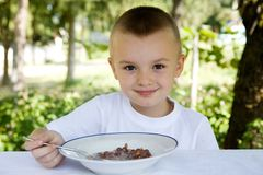 Breakfast. Little boy is heaving cereal for breakfast royalty free stock images