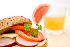 Breakfast. Sandwich on dark bread with cheese, sausage and tomato and orange juice Stock Images