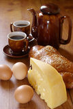 Breakfast. Piece of cheese, eggs, bun, coffee-pot and two cup of coffee on brown wood surface Stock Images