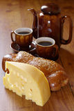 Breakfast. Piece of cheese, eggs, bun, coffee-pot and two cup of coffee on brown wood surface Royalty Free Stock Images