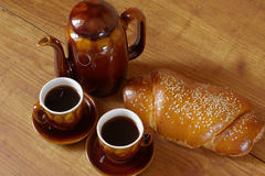 Breakfast. Bun, coffee-pot and two cup of coffee on brown wood surface Stock Photo