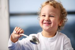 Breakfast. Portrait of the little boy eating yogurt Stock Image